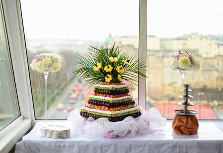 receptions: Sweet pyramid with fruits and fondue on the white table on the wedding banquet Stock Photo