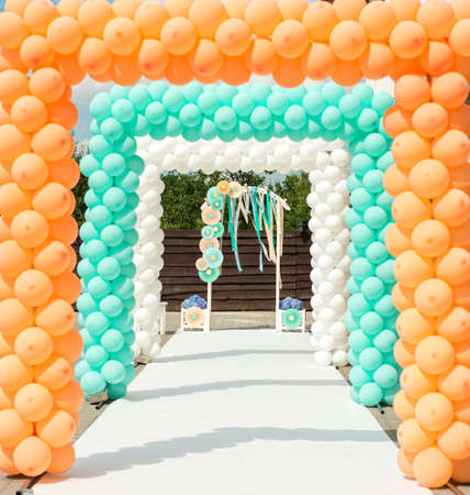arch: Balloon and paper arches like decorations for wedding ceremony in orange and blue colors
