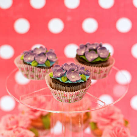 butter icing: Delicious cupcakes with flowers on the glass plate