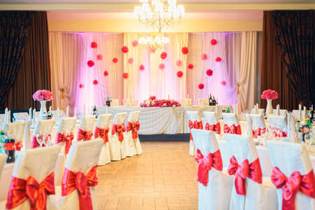 Beautifully decorated elegant restaurant with pink flowers and ribbons for celebration wedding or event Imagens