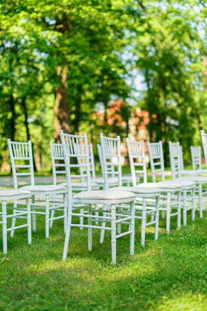 wedding chairs: White wedding chairs set up on green grass before the ceremony