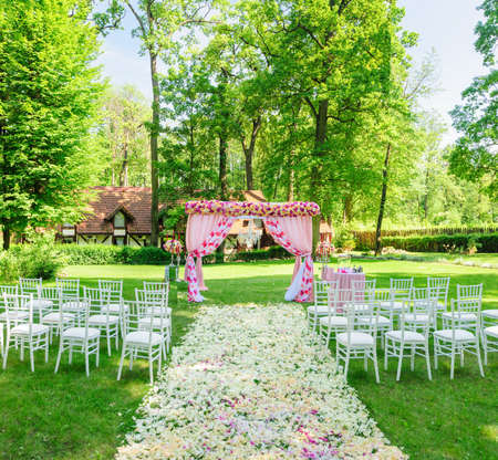 All is ready for elegant wedding ceremony in the summer garden: chairs, petals and arch
