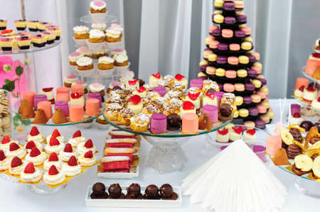 Wedding decoration with colorful cupcakes, eclairs, souffle, meringues, muffins and macarons. Elegant and luxurious event arrangement with sweets. Wedding dessert table