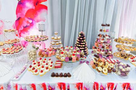 postres: Decoración de la boda con coloridos cupcakes, eclairs, soufflé, merengues, magdalenas, macarons y galletas. Disposición evento elegante y lujoso con dulces. Vector de la boda postre en colores rosa Foto de archivo