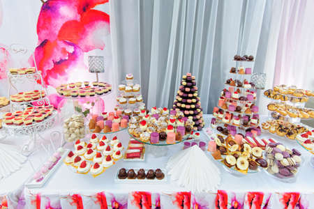 Wedding decoration with colorful cupcakes, eclairs, souffle, meringues, muffins, macarons and cookies. Elegant and luxurious event arrangement with sweets. Wedding dessert table in pink colors