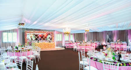 Incredibly beautiful wedding venue in a restaurant with a lot of flowers  All is ready for wedding celebrations in luxury restaurant: covered tables with a lot of flowers in pink tones Imagens