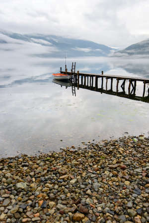 fiord: Boat near wooden pier in a norwegian fiord in cloudy weather. Amazing nature of Norway