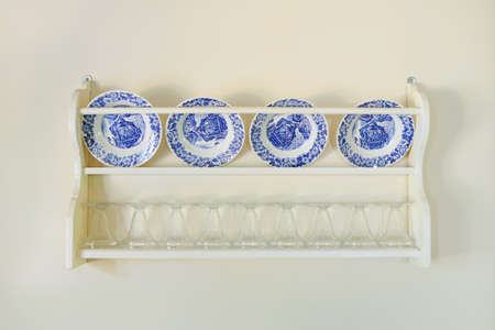 blue white kitchen: white plates with blue pictures on the shelf, kitchen cooking utensils. Stock Photo