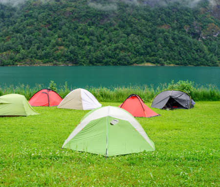 norwegian: Colorful tents near Norwegian fjord  travel background