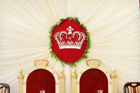 royal wedding: White crown on red background like decoration for the royal wedding under the table