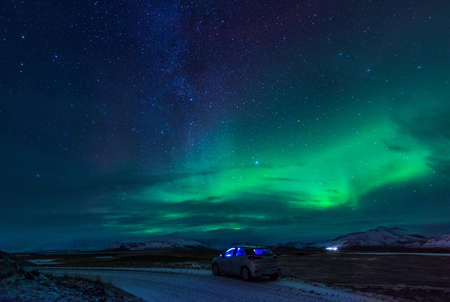 Night road with travel car in Iceland with amazing green northern lights
