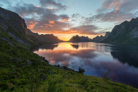 great bay: Beautiful sunset near the great mountains and clear silence water at Reine, Bunesfjorden, Lofotens. Amazing nature of Norway. Cloudscape Stock Photo