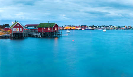 fishing hut: Scenic landscape on Lofoten islands, Reine with typical red fishing hut with grass on the roof near water in the evening Stock Photo