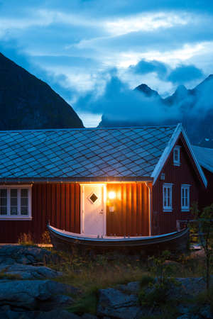 fishing hut: typical Norway red fishing hut with fishing wooden boat in the evening near great mountains Stock Photo