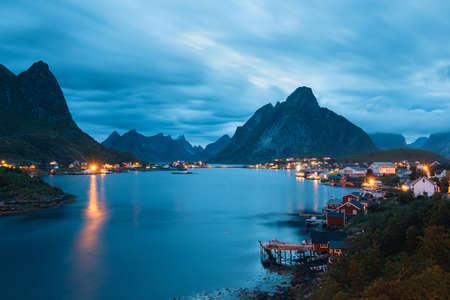 風景: ロフォーテン諸島の風光明媚な風景、夕方には水の近くの屋根の上の草と典型的な赤釣り小屋とレーヌ