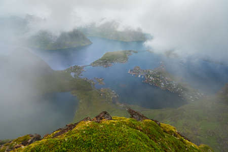rorbu: Scenic landscape of Lofoten islands: peaks, lakes, clouds and houses. Reine village, rorbu, reinbringen Stock Photo
