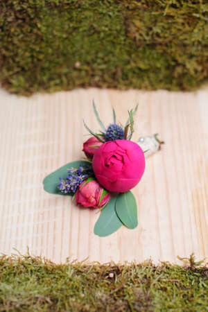 bonbonniere: Beauty of colored flowers. Bridal accessories. Close-up bunch of florets. Details for marriage and for married couple. Wedding bonbonniere for the groom on wooden background