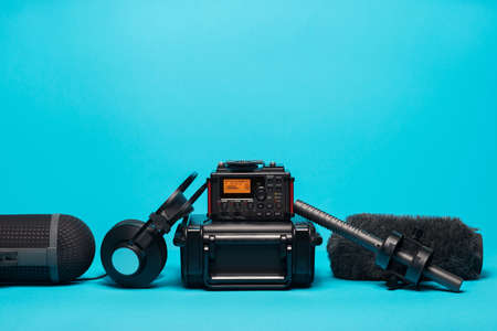equipment for field audio recording on blue background. Windshield, shotgun microphone,  recorder, portable case and headphones Stockfoto