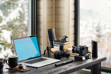 Audio  Video editing workspace office with mountain view. Photography and videography equipment.