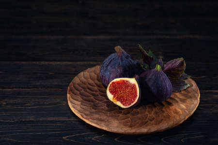 A few figs on a plate on an black wooden background. Healing Fruit