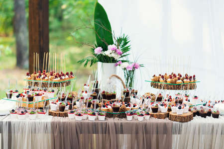 Delicious sweets on candy buffet. Lot of colorful desserts with strawberry, and raspberry.