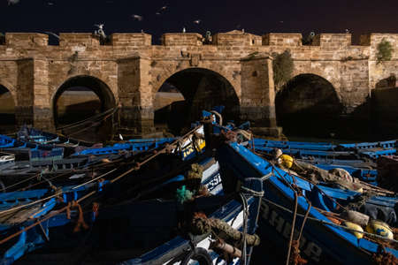 Fishing port of Essaouira at the night time, Morocco. Blue ships in the night port of Essaouira Editorial