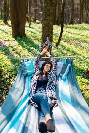 Young beatifull girl in hammock enjoying sunny weekend somewhere in green spring wood