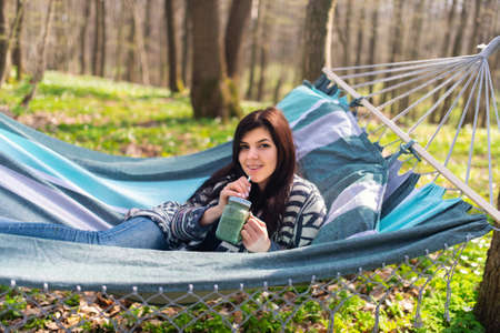 Happy healthy eating girl drinking green smoothie detox outdoors in hammock. Woman on weight loss diet vegan nutrition cleanse.