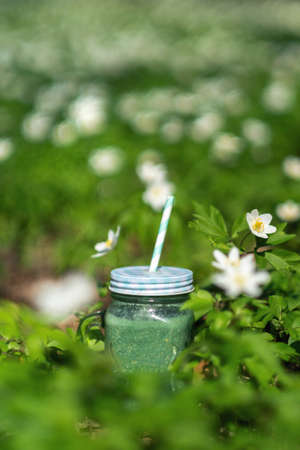Freshly blended green fruit smoothie in glass jar with straw