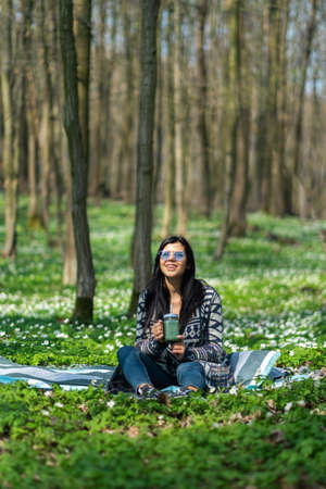 Happy healthy eating girl drinking green smoothie detox outdoors in the wood. Woman on weight loss diet vegan nutrition cleanse. Imagens
