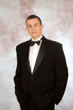 Portrait the man in a classical tuxedo on an abstract background photo