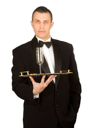 The imposing man in a classical tuxedo with a wine glass on a tray