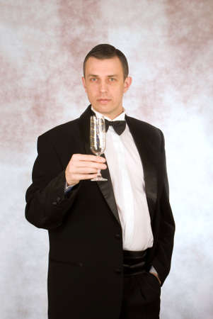 The imposing man in a classical tuxedo with a wine glass photo
