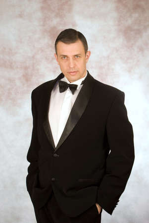 Portrait the man in a classical tuxedo on an abstract background
