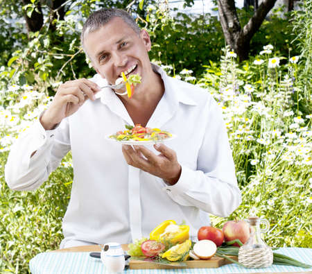 The man the vegetarian eats salad from fresh vegetables photo