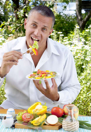The man the vegetarian tastes salad from fresh appetizing vegetables photo
