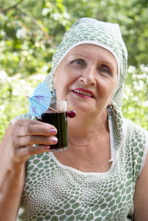 The happy smiling woman drinks fresh cherry juice Stock Photo - 14199642
