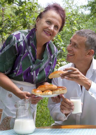 The happy family eats baked house pies with fresh milk in a summer garden Stock Photo - 14232935