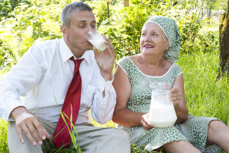 Happy seniors mother treats the son of the businessman with pair milk in a summer garden Stock Photo - 14345451