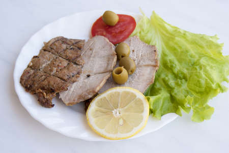 Appetizing fried meat with vegetables and olives
