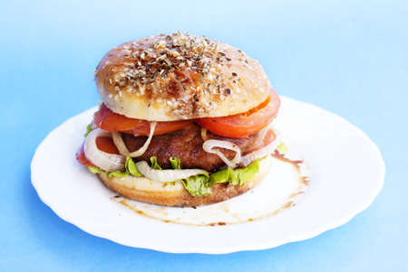 Burger with meat and baked vegetables on a blue background photo