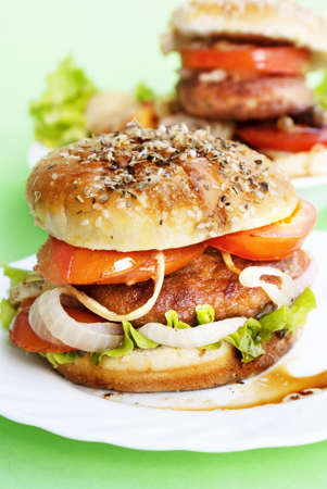Burger with meat and baked vegetables on a light green background photo