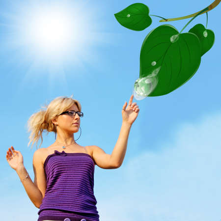 Young beautiful woman and green globe planet in clean drop water upon leaf tree photo