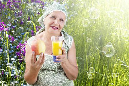 Adult female with fresh ripe apple and orange juice on a nature photo