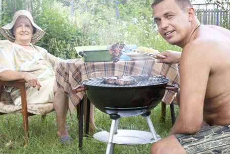 Happy family preparing a barbecue in the summer garden photo