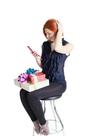 Happy girl on a chair with a telephone and a gift box on a white background photo
