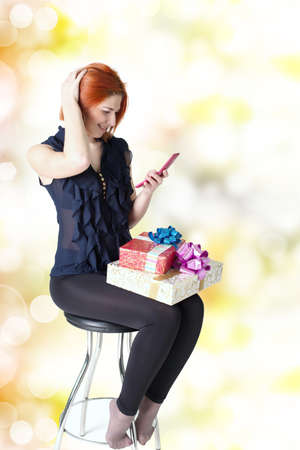 Happy girl on a chair with a telephone and a gift box photo