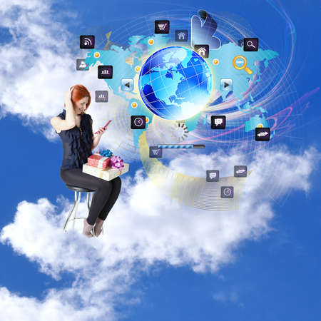 Happy red-haired girl with gifts and a phone in cloud dreams on chair Internet shopping photo