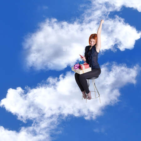 Happy red-haired girl with gifts and a phone in cloud dreams on a chair photo