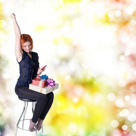 Happy red-haired girl with gifts and phone on a chair at a festive abstract background photo